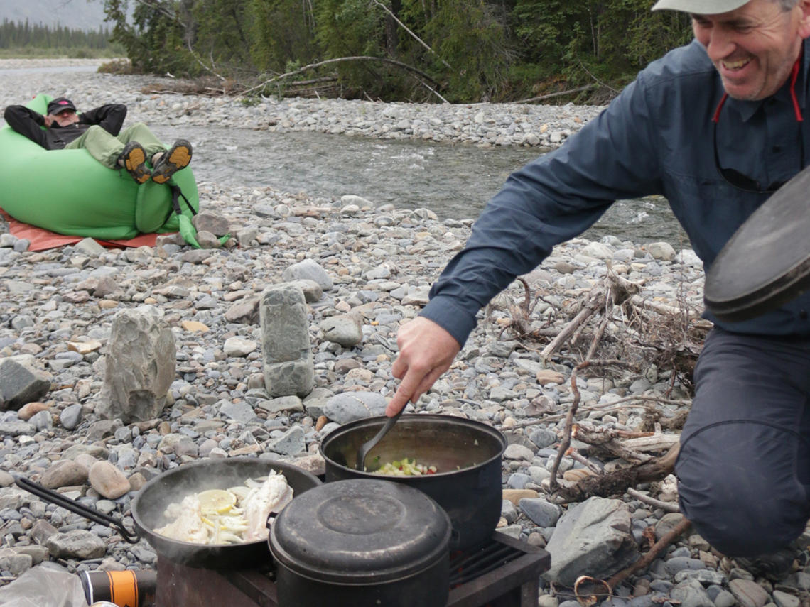 Paddler stirring backcountry meal on the banks of a river