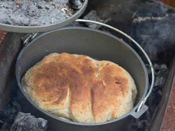 Backcountry cooking dutch oven bread over open fire